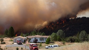 Firefighters protect an evacuated home near the fast moving wildfire.