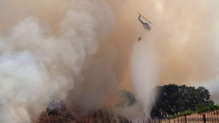 "A helicopter drops water on the fast-moving wildfire called ""Sand Fire."""