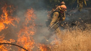 A firefighter battles the flames in east California.