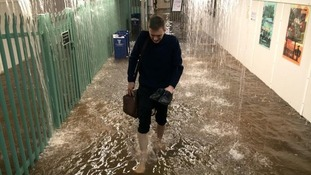 A commuter tries to make his way through Worthing Station in wellies.