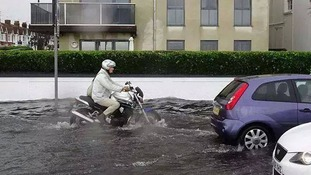 A motorcyclist struggles through flood water in Worthing.