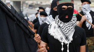 Refugees, wearing Palestinian traditional headscarves and carrying black flags, attend a demonstration calling for an end to the Israeli offensive.