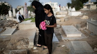 A woman and girl carry flowers to a family grave.