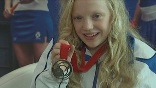 Para-sport swimmer Erraid Davies smiles as she shows her bronze medal.