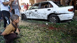 A boy looks at a damaged car after an explosion at a public garden in Gaza.