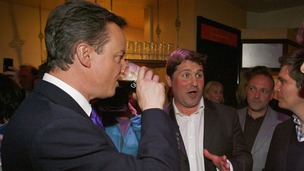 British Prime Minister David Cameron sinks a pint of Guinness.