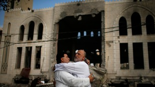 Palestinians stand in front of a mosque which witnesses said was hit in an Israeli air strike.