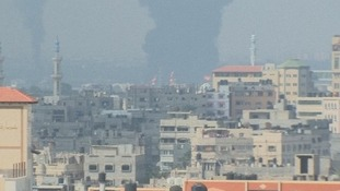 The Gaza Strip's only power plant can be seen ablaze in the distance.