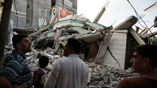 Palestinians stand by the rubble of the home of Hamas leader Ismail Haniyeh.