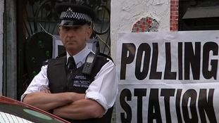 Police officer outside a Tower Hamlets polling station