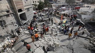 Palestinian rescue workers search for bodies amid the rubble of a house in Khan Younis, southern Gaza.