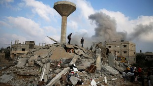 Palestinians search for victims as people gather atop the remains of a house in Rafah, southern Gaza.