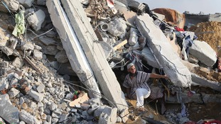 A Palestinian man searches for victims under the rubble of a house in Rafah, in the southern Gaza strip.