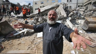 A Palestinian man reacts as rescue workers search for victims under the rubble of a house in Khan Younis, in southern Gaza.