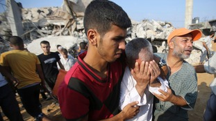 A Palestinian man reacts as people search for victims under the rubble of a house, which witnesses said as destroyed by an Israeli airstrike.