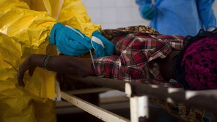 Medical staff take a blood sample from a suspected Ebola patient in Sierra Leone.
