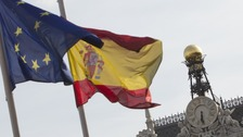 European and Spanish flags flutter next to the Bank of Spain in Madrid.