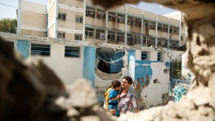 A man carries a child through the remains of a classroom being used as a UN shelter in Gaza.