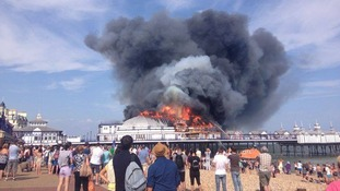 Holidaymakers and locals watch on as fire crews tackle the blaze on Eastbourne Pier.