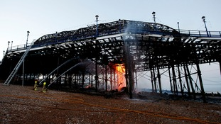 Firemen continue to tackle the final flames of a fire at Eastbourne Pier on Wednesday evening.
