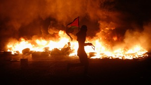 A Palestinian protester holds a flag as he runs past burning tyres during clashes with Israeli troops.