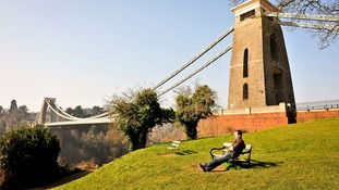A man relaxes on a bench in the mid-morning sun by Clifton Suspension Bridge, Bristol.