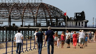 The public view the the fire-ravaged Eastbourne Pier after a blaze swept through the dome shaped amusement arcade yesterday.