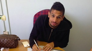 Kevin Bru signs his contract at Portman Road.