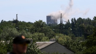 Smoke rises above a damaged multi-storey block of flats following what locals say was shelling by Ukrainian forces in Shakhtarsk on 28 July.