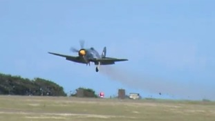 Smoke billows from The Royal Navy Sea Fury aircraft as it makes an emergency landing on the runway
