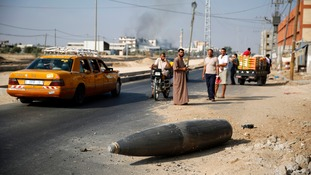Palestinians look at an unexploded Israeli shell that landed near Deir Al-Balah in the central Gaza Strip.