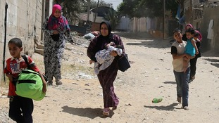 Palestinian women and children run from shelling in Rafah, eastern Gaza Strip.