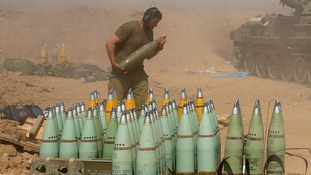 An Israeli soldier carries a shell at a mobile artillery unit as it fires on the Gaza Strip.