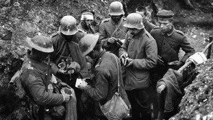 British troops sort through the belongings of German prisoners in a trench, with articles being placed in an empty sand bag
