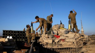 Israeli soldiers load shells on to a tank near the Gaza Strip.
