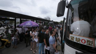 People line up in front of a bus to donate blood for the victims of the explosion.