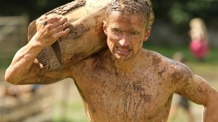 man carries log covered in mud