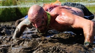 man crawls under barbed wire through thick mud