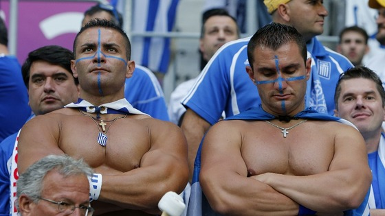 Two dejected Greece fans struggle with defeat by the Czech Republic.