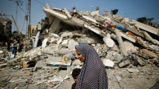 A Palestinian woman walks past the rubble of a home.