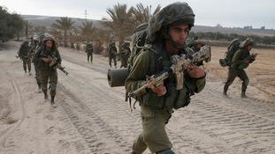 Israeli soldiers seen walking near the Gaza Strip.