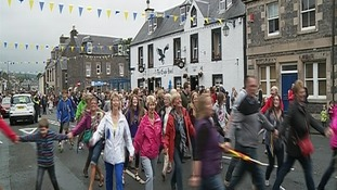 Crowds dance up the High Street.