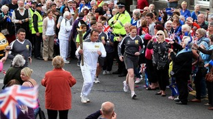 Callum Gordon carries the Olympic Flame on the Torch Relay leg between Scone Palace and Newburgh.