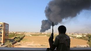 A fighter from Zintan brigade watches as smoke rises after rockets fired by militia ignites a fuel tank.