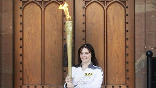 16-year-old Louise Fox holds the Olympic flame.