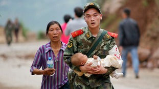 A paramilitary policeman carries a baby in his arm after the quake which hit 6.3 on the richter scale.
