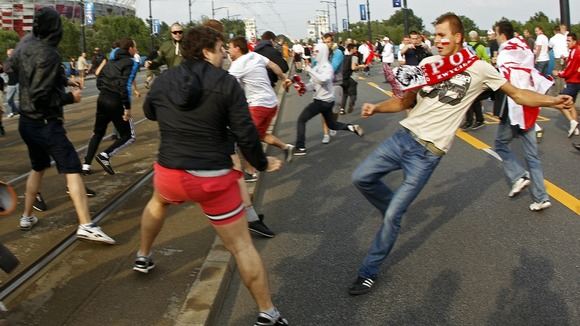 A Polish supporter challenges Russian football fans in Warsaw.