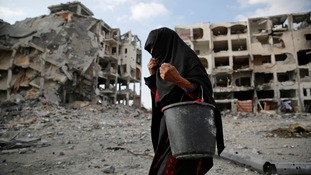 A Palestinian woman searches for water amid buildings destroyed by Israeli air strikes and shelling in Beit Lahiya