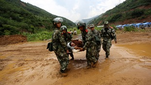 Paramilitary policemen carry an injured man through a muddy road after an earthquake hit. Although the death toll has risen, rescuers have found scores of survivors.