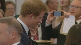 Someone takes a photograph of Prince Harry as he mingles at the St Symphorien event.